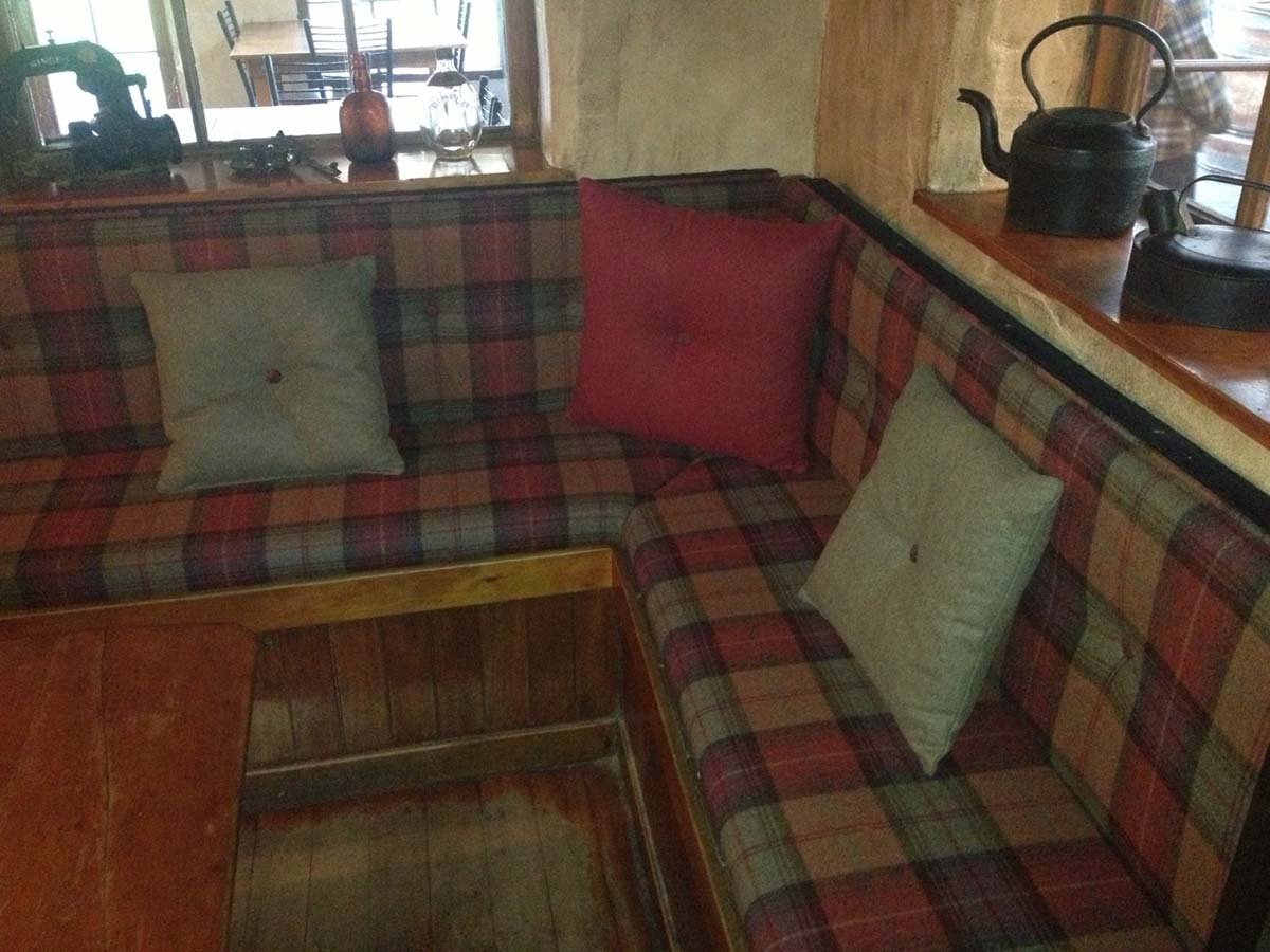 Seating and cushions in plain and Tartan wool fabric for Cardrona Hotel
