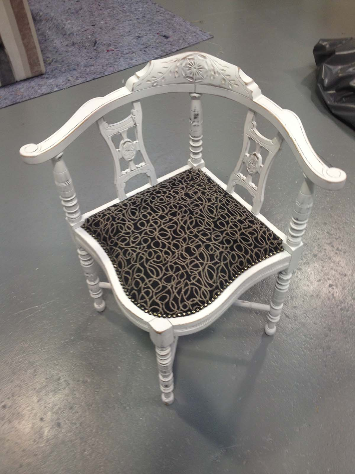 Antique corner Chair finished with a distressed white paint and black and white scrolled fabric.